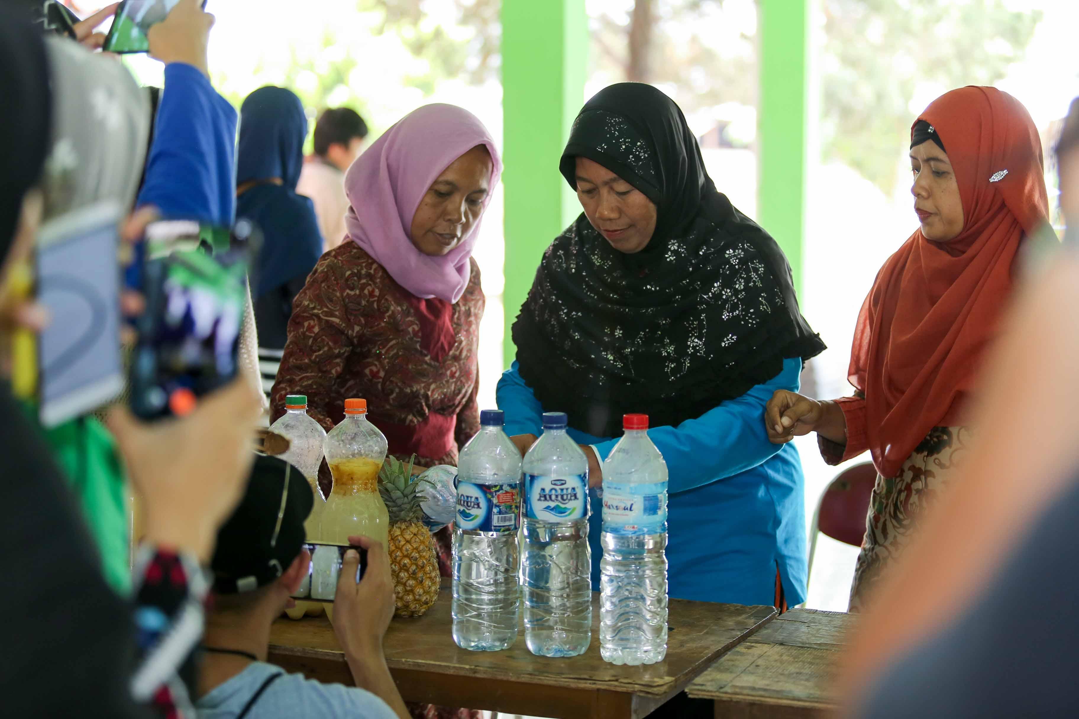 Ibu-ibu sedang memeragakan cara membuat pupuk cair dari sampah dapur.